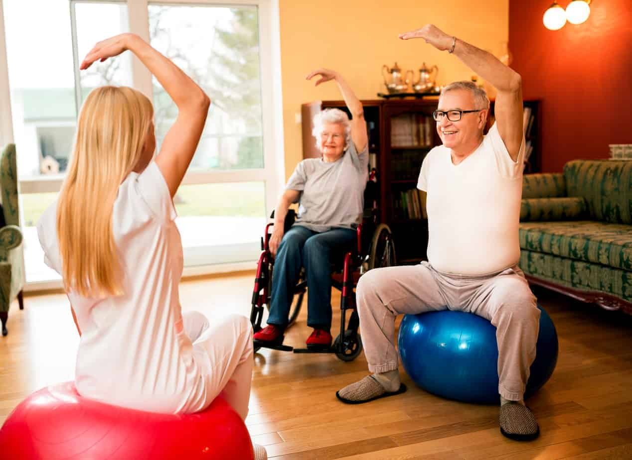 senior people exercise with physiotherapist chair exercise